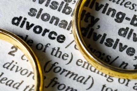 Twee aparte trouwringen naast het woord echtscheiding. Stockfoto