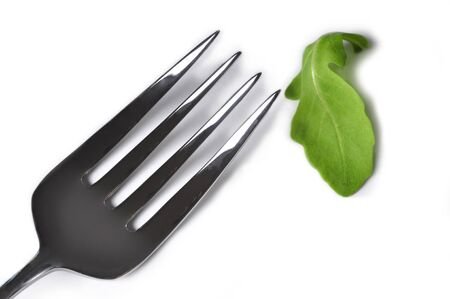 deprived: A fork  next to a rucola leaf to illustrate the concept of diets Stock Photo