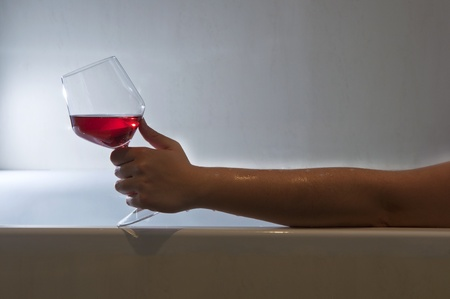 woman in bath: Woman taking a bath and relaxing with a glass of wine Stock Photo