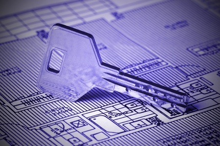 A key rests on top of a house blueprint. The overall image tone is blue and there Stock Photo - 10361099
