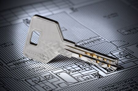 obtain: A key rests on top of a house blueprint. The overall image tone is blue and there Stock Photo