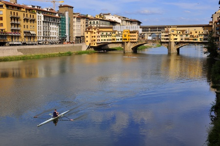 medici: Vecchio Bridge , Florence , Italy, with rower passing by Stock Photo