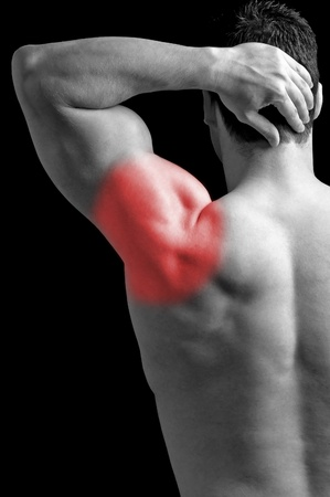 aching muscles: Bodybuilder suffering from shoulder pain.