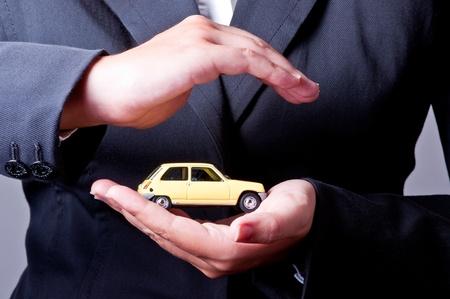 서로 마주 보는 두 손, 노란 차를 보호합니다.