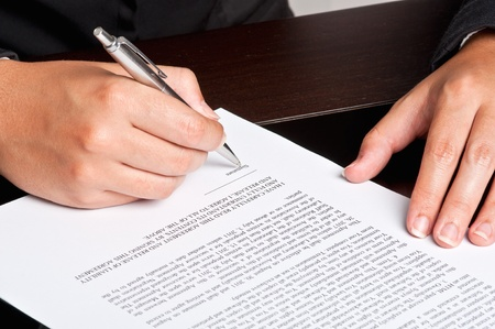 Businesswoman signing a document. photo