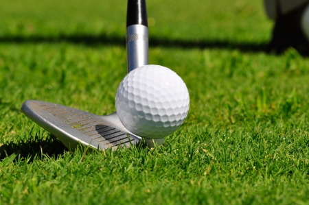 golf swings: Golf ball and driver, ready to strike, on a real golf course. Stock Photo
