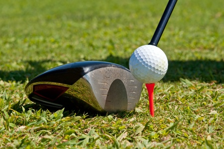 golfball: Golf ball and driver, ready to strike, on a real golf course. Stock Photo