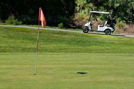 골프 코스에 구멍 옆에 골프 카트 스톡 사진