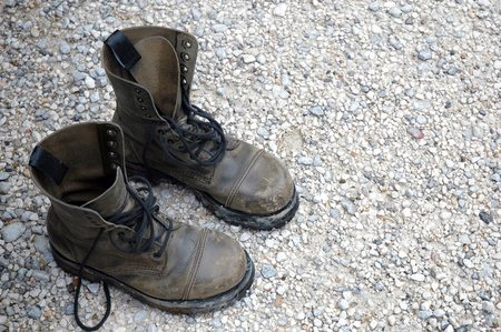Old worn boots on a rocky floor photo
