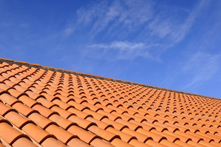 roof tile: Orange roof tiles made from a ceramic material and the sky above