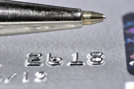 Closeup of a credit card with a silver pen on top of it photo