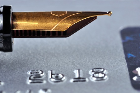 Closeup of a credit card with a golden fountain pen on top of it photo