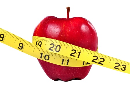 Red apple and yellow measuring tape to symbolize an healthy diet and body weight control. photo