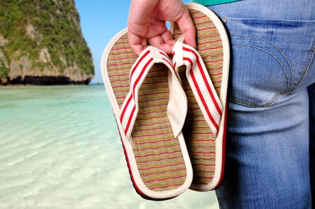 flip flops: Girl holding sandals on the first day of vacations at the beach.