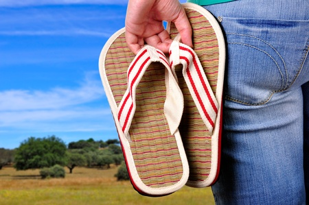 sandal tree: Girl holding sandals on the first day of vacations at the country. Stock Photo