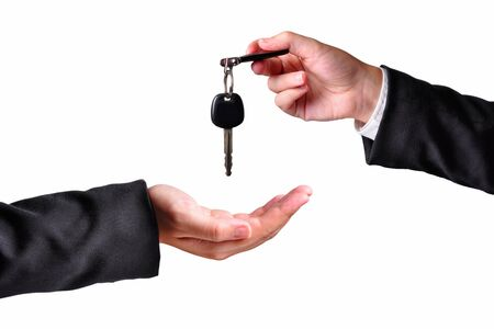homebuyer: A hand giving a key to another hand. Both persons in suits. Isolated.