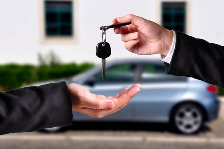 A hand giving a key to another hand. Both persons in suits. Car in the background. Stock Photo