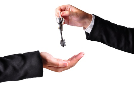 A hand giving a key to another hand. Both persons in suits. Isolated. Stock Photo - 10811362