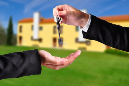 homebuyer: A hand giving a key to another hand. Both persons in suits. House in the background.