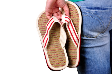flip flops: Girl holding sandals on the first day of vacations. Isolated. Stock Photo