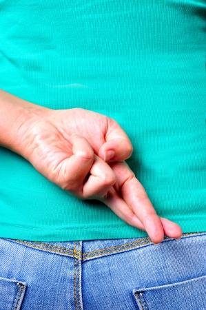 Primer plano de los dedos cruzados detrás de la espalda de una mujer