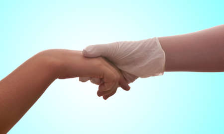 latex glove: A hand with a medical latex glove holds another hand Stock Photo