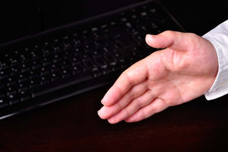 Hand ready for an handshake next do a computer keyboard on a dark table Stock Photo - 11031836