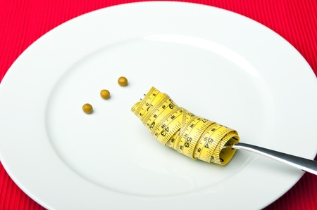 low calorie: Plate with three peas and a measuring tape around a fork.