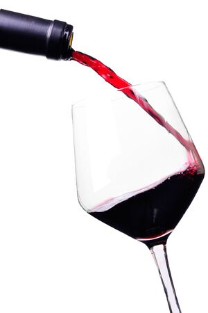 red wine pouring: Bottle pouring red wine into a wine glass Stock Photo