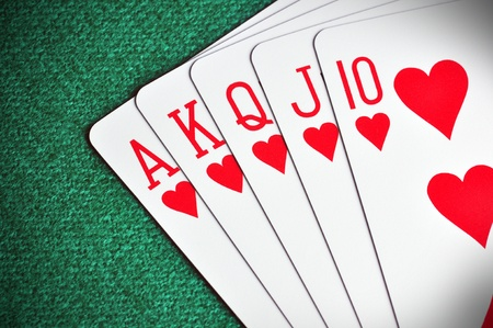 card game: Royal Flush poker card sequence on a green table Stock Photo