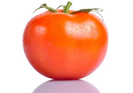 Een rode tomaat met druppels water op een witte achtergrond met een reflectie hieronder