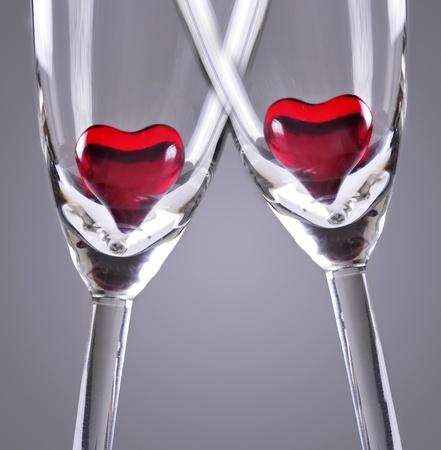 Rode gelei harten in champagneglazen, grijze achtergrond Stockfoto