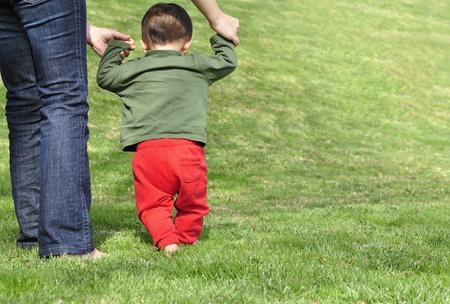 Baby van het maken van de eerste stappen met de hulp van zijn moeder