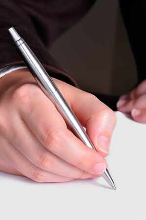 A hand, holding a pen, is ready to write on a document photo