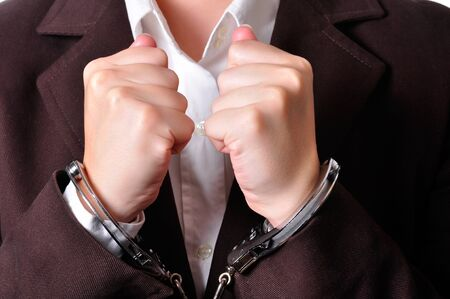 cuffed: Closeup of an handcuffed businessperson in a brown suit Stock Photo