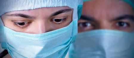 vignetting: Closeup portrait of two surgeons during a surgery. Blue cast and vignetting applied.