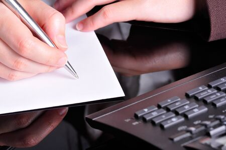 A hand, holding a pen, is ready to write on a document with a telephone next to it  photo