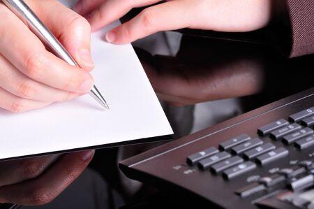 document management: Una mano, la celebración de una pluma, está listo para escribir en un documento con un teléfono al lado de él
