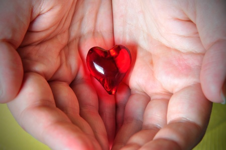 Glowing red heart hold on the palm of one photo