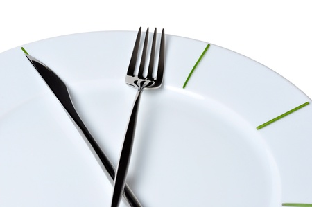 meal preparation: Clock made of knife and fork, isolated on white background