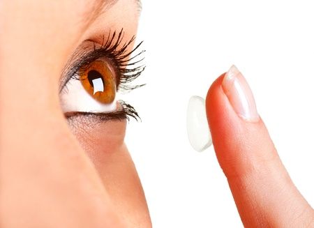 Closeup of a woman inserting a contact lens in her eye Stock Photo