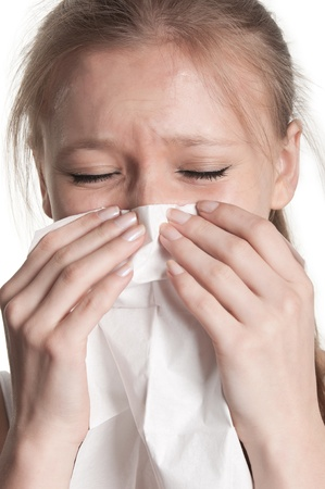 Pale sick woman with a flu, sneezing, in a white background