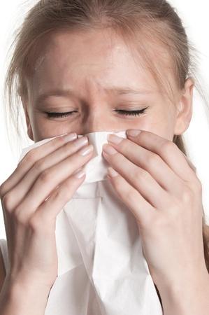 Pale zieke vrouw met een griep, niezen, in een witte achtergrond