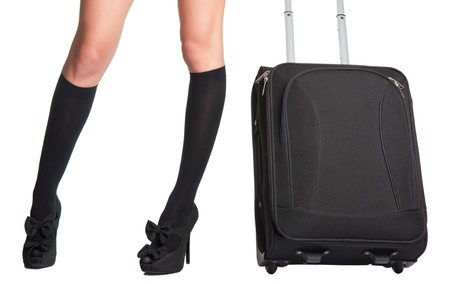 Businesswoman s legs in high stockings and high heels, holding a black suitcase photo