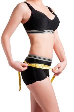 노란색 측정 테이프와 그녀의 허리를 측정하는 여자