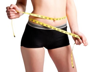 cintas metricas: Mujer medir su cintura con una cinta métrica amarilla Foto de archivo