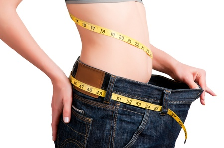 lose: Woman seen how much weight she lost. Isolated background. Stock Photo