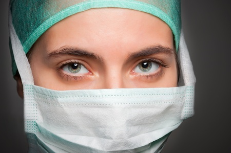 Closeup portrait of a female surgeon, with face mask, in a dark grey background Stock Photo - 13713524