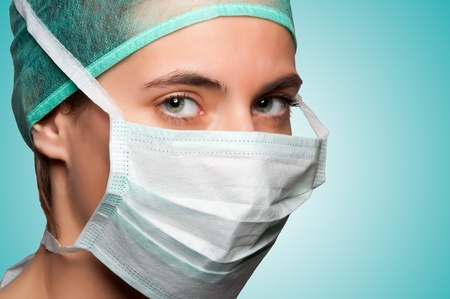 Closeup portrait of a female surgeon in a green background photo