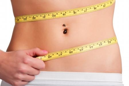 허리의 잘룩 한 선: 노란색 측정 테이프와 그녀의 허리를 측정하는 여자